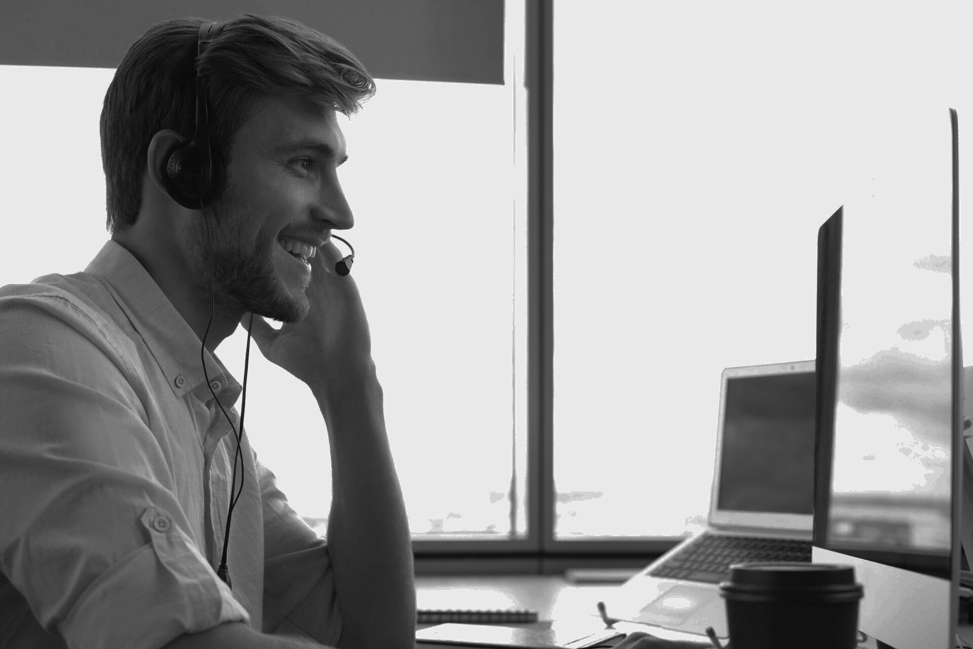 homme souriant au travail avec un casque téléphonique professionnel passant des appels